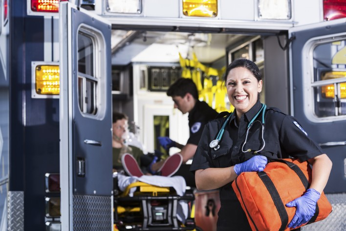 Hispanic female paramedic (30s).  Male paramedic helping boy inside ambulance behind her.