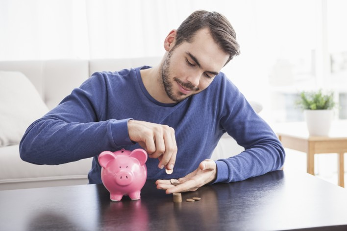 Young-man-putting-coins-in-piggy-bank-000053497424_Large