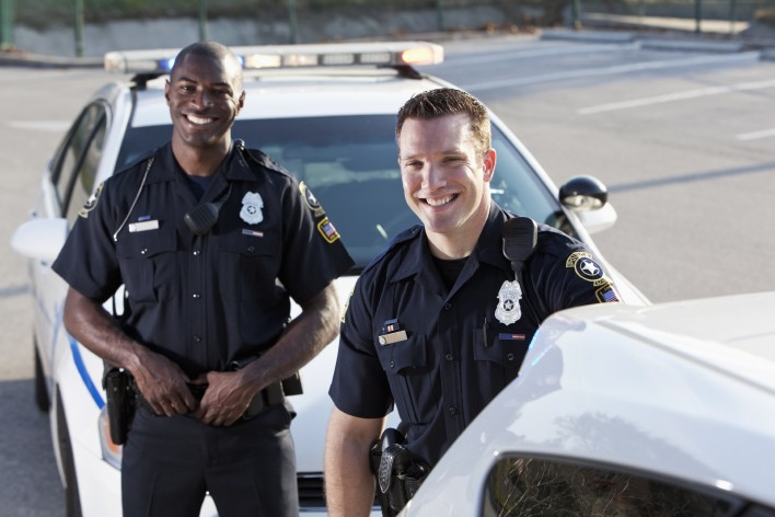 Multi-ethnic police officers (20s) standing in front of police car.  Focus on Caucasian man.